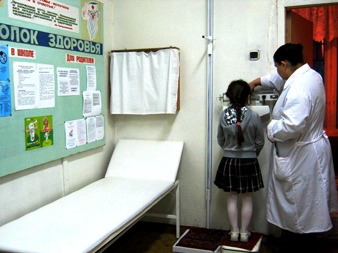 Обычный медицинский кабинет с пациентом и медсестрой.