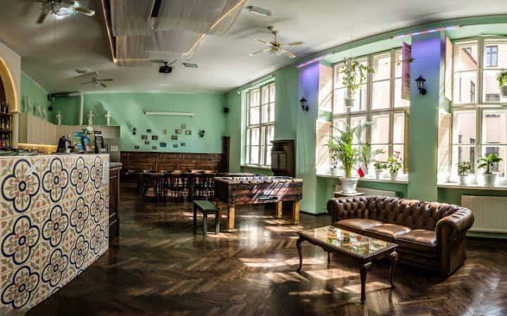 Уютная гостиная в заграничном хостеле, с баром, настольным футболом, кожаными креслами и столами в цвет дизайна.
