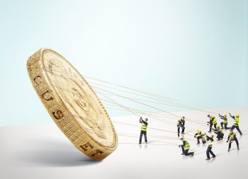 Group of builders carrying a large gold Pound coin